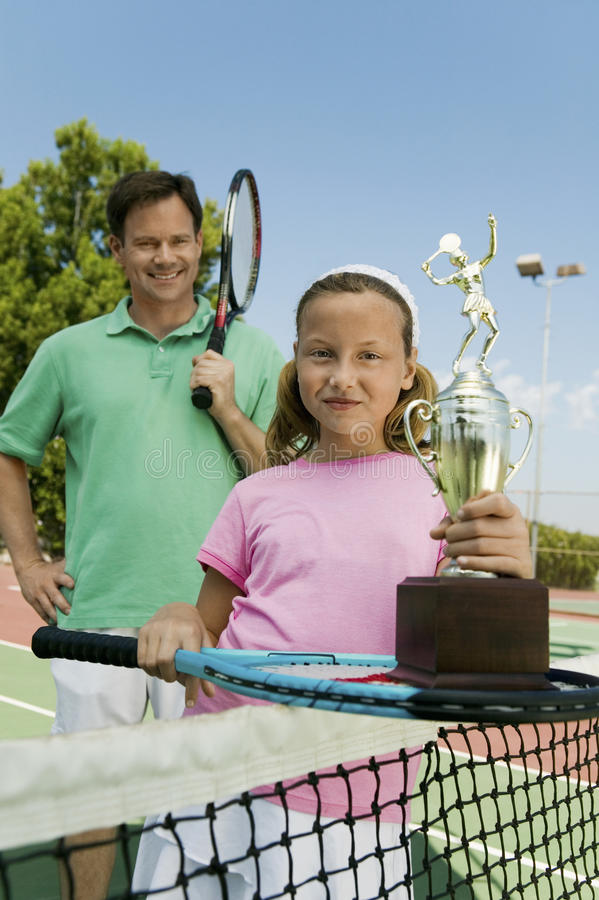父亲和女儿由网在拿着球拍和战利品画象的网球场 免版税库存照片