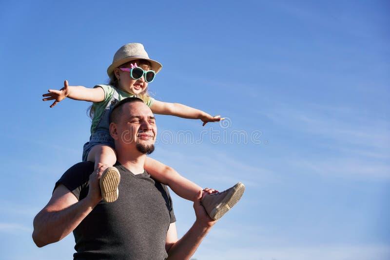父亲和女儿肩膀的愉快地高兴 拿着一点女儿的爸爸坐仿造物教皇的飞行 免版税库存图片