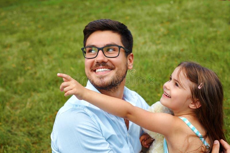 父亲和女儿获得乐趣在公园 放松的系列户外 免版税库存照片