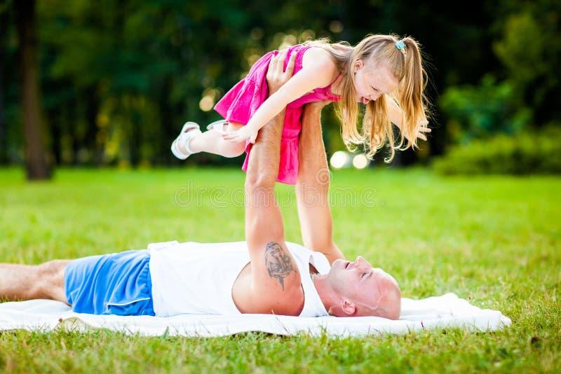 父亲和女儿获得乐趣在公园 免版税库存照片