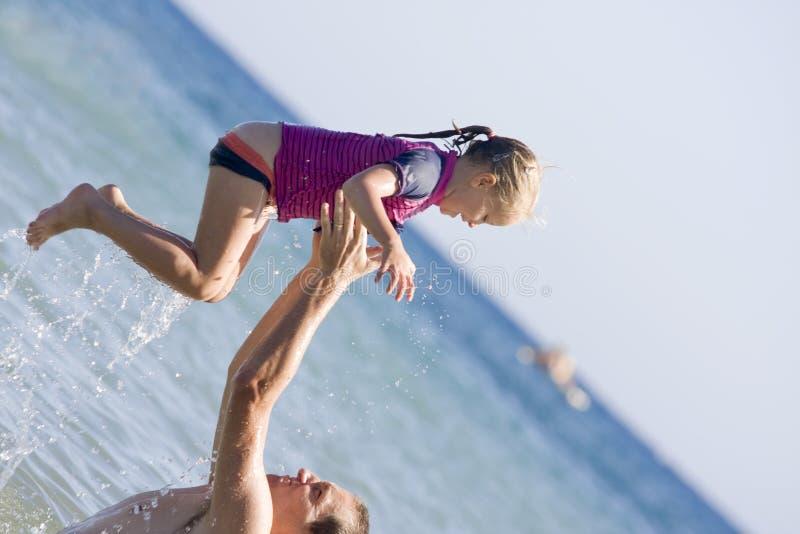 父亲和女儿获得乐趣在海洋 免版税图库摄影