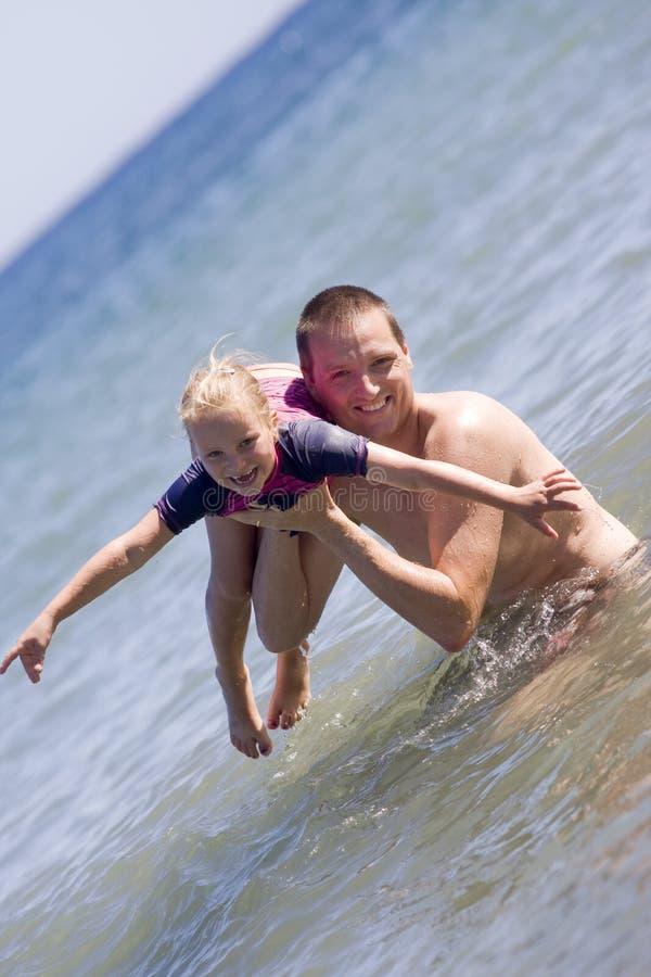 父亲和女儿获得乐趣在海洋 库存图片
