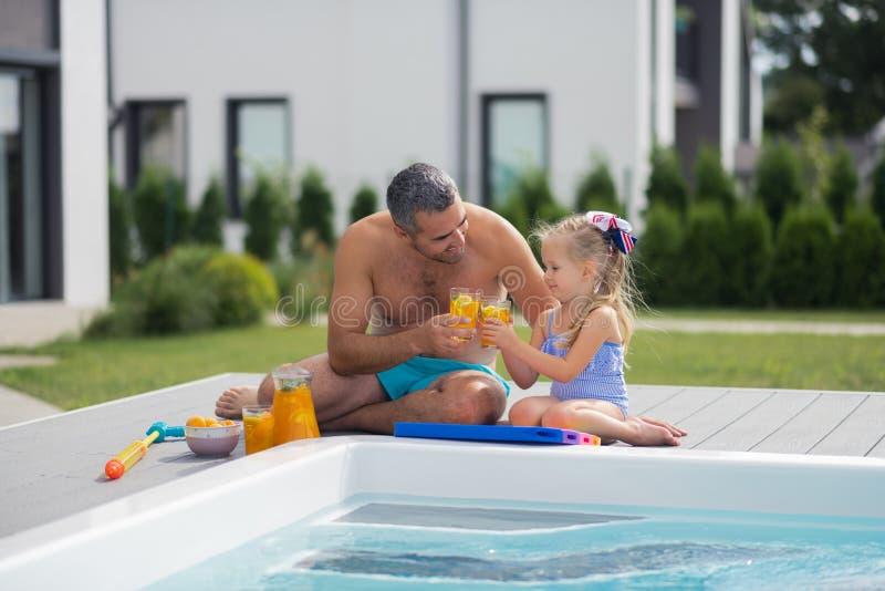 父亲和女儿饮用的汁液,当变冷在水池附近时 库存照片