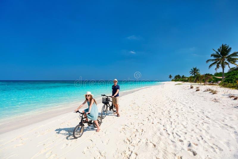 父亲和女儿骑马骑自行车在热带海滩 库存照片