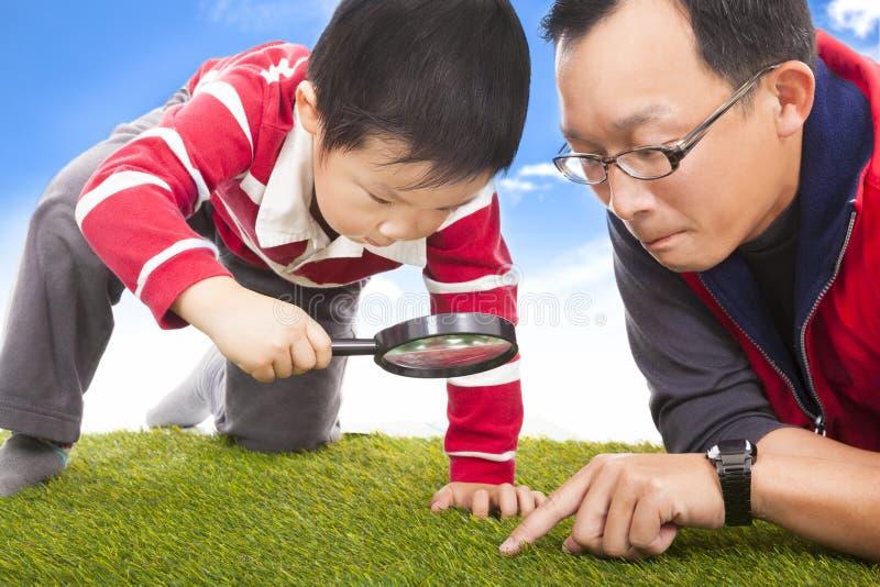 父亲和孩子与发现的放大镜 免版税图库摄影