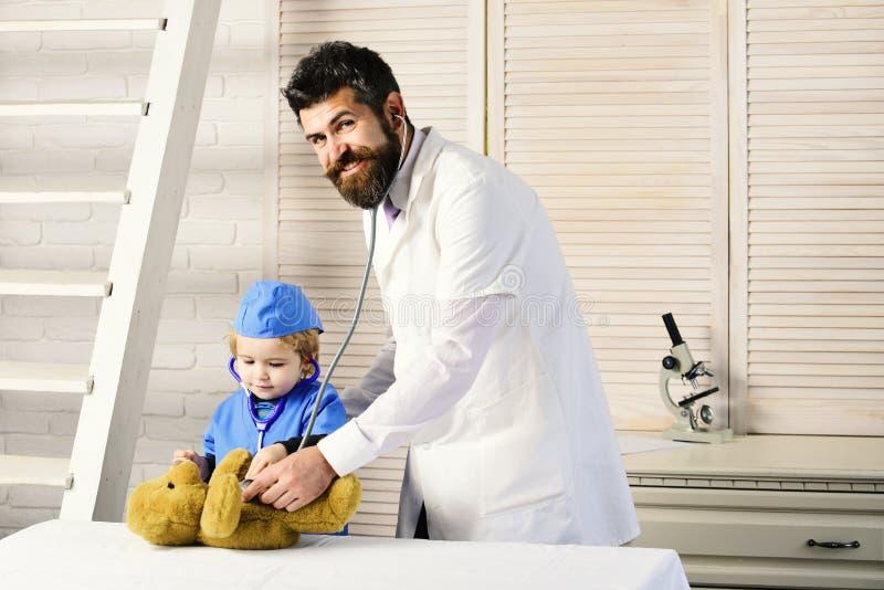 父亲和孩子与愉快的面孔扮演医生 免版税库存图片