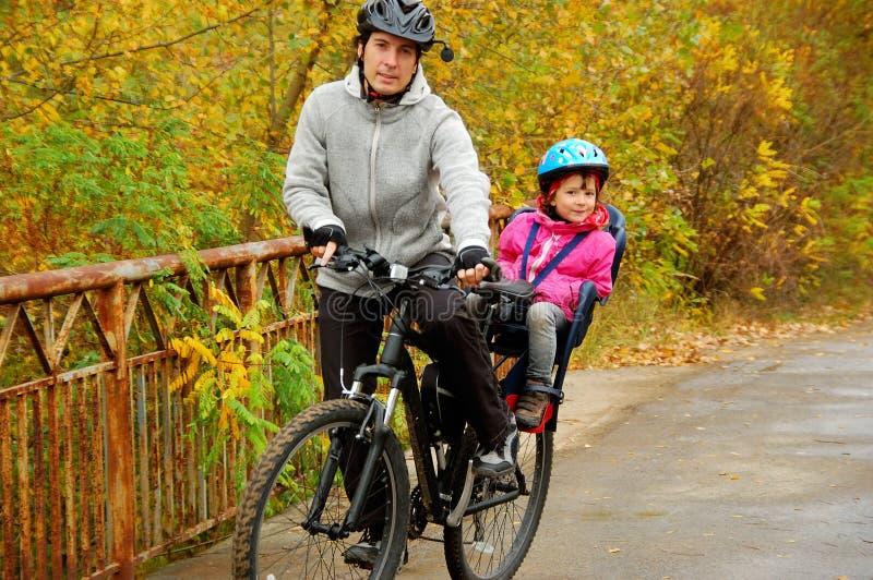父亲和孩子在自行车,循环在秋天公园 库存图片