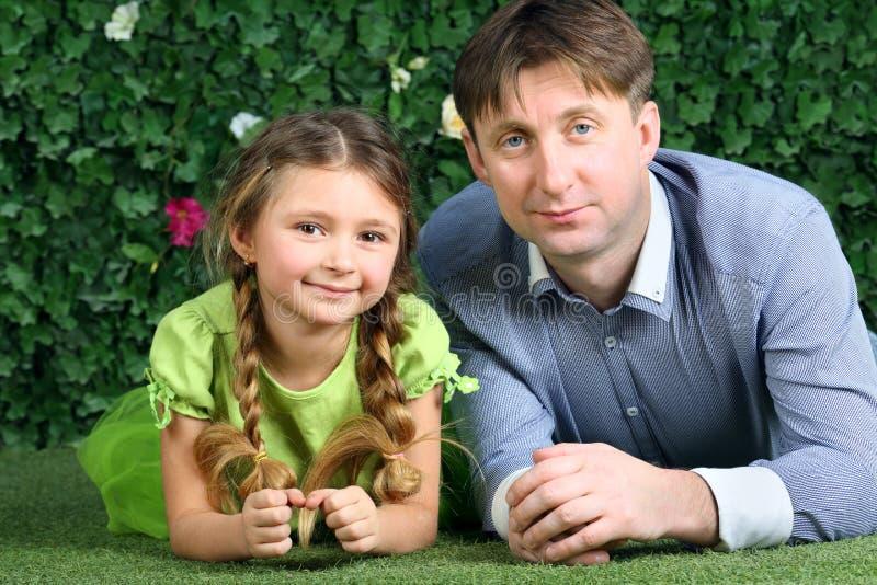 父亲和小女儿在绿草说谎 免版税图库摄影