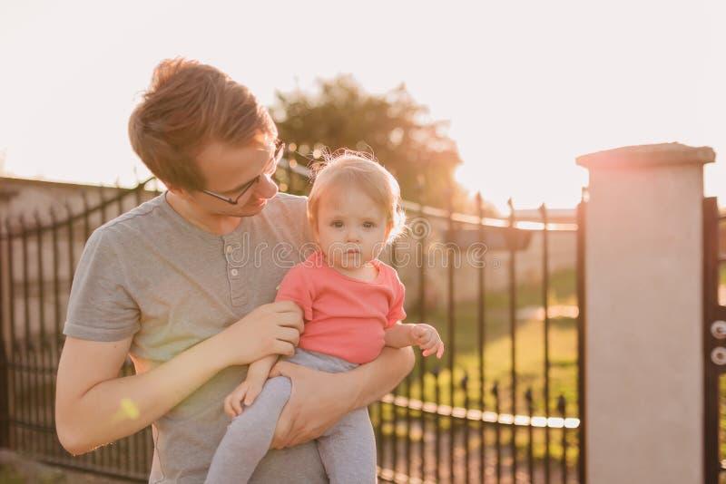 父亲和小女儿外面日落的 库存照片