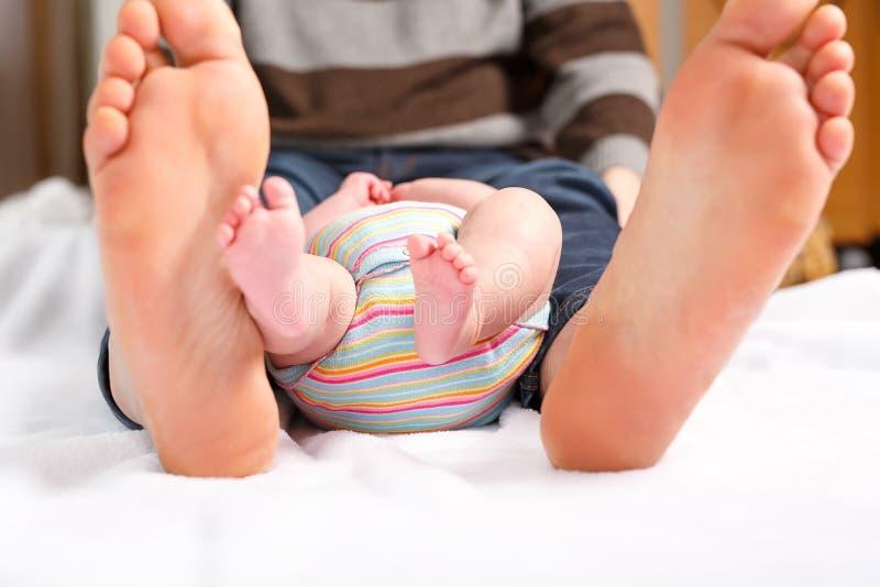 父亲和小新出生的婴孩的巨大的脚特写镜头  孩子的成人和微小的腿的大脚 愉快的父母身分 库存图片
