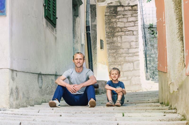 父亲和小的儿子选址在老克罗地亚镇街道上 库存图片