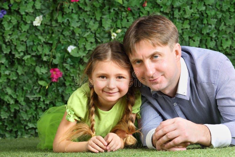 父亲和小的女儿谎言在草 免版税库存照片