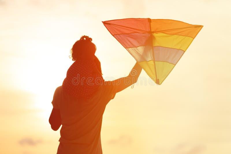 父亲和小的女儿飞行风筝在日落 库存照片