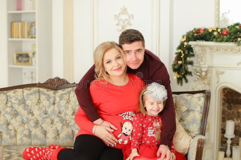 父亲和怀孕的母亲与小女儿坐近沙发装饰了壁炉 免版税库存图片