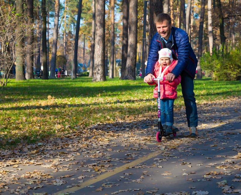 年轻父亲和愉快的儿童骑马反撞力滑行车在公园 免版税图库摄影