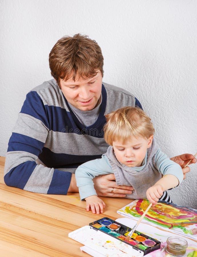 父亲和有二的年的小男孩乐趣绘画 免版税库存照片
