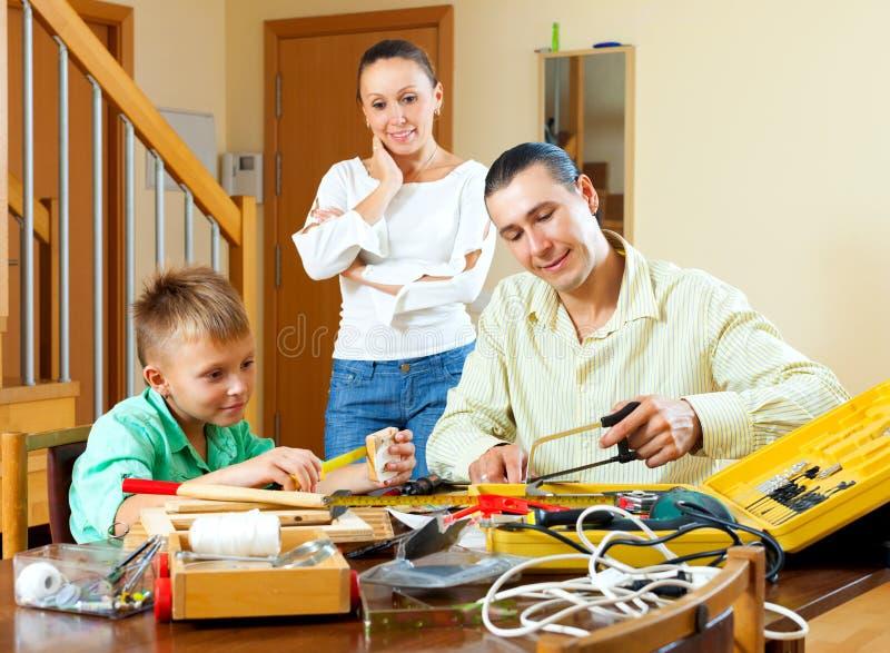 父亲和男孩在家花费他们的与工具的业余时间 库存图片