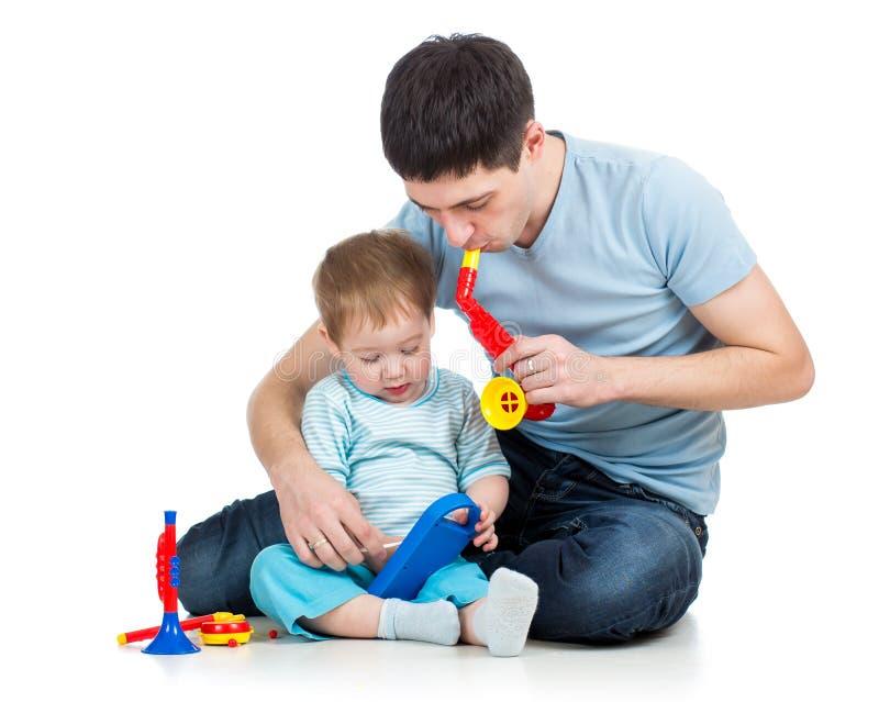 父亲和获得的男婴与音乐玩具的乐趣 库存图片