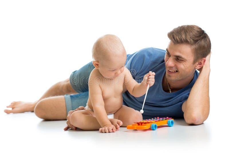 父亲和获得的男婴与音乐玩具的乐趣 隔绝在wh 免版税库存照片