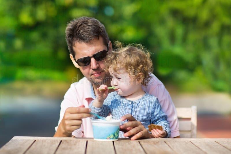 年轻父亲和他的享用冰淇凌的小女儿 库存图片