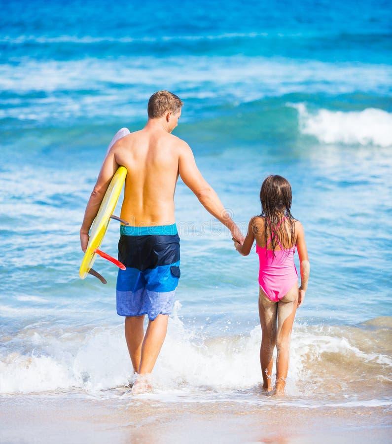 父亲和Duagher在海滩去的冲浪 免版税图库摄影