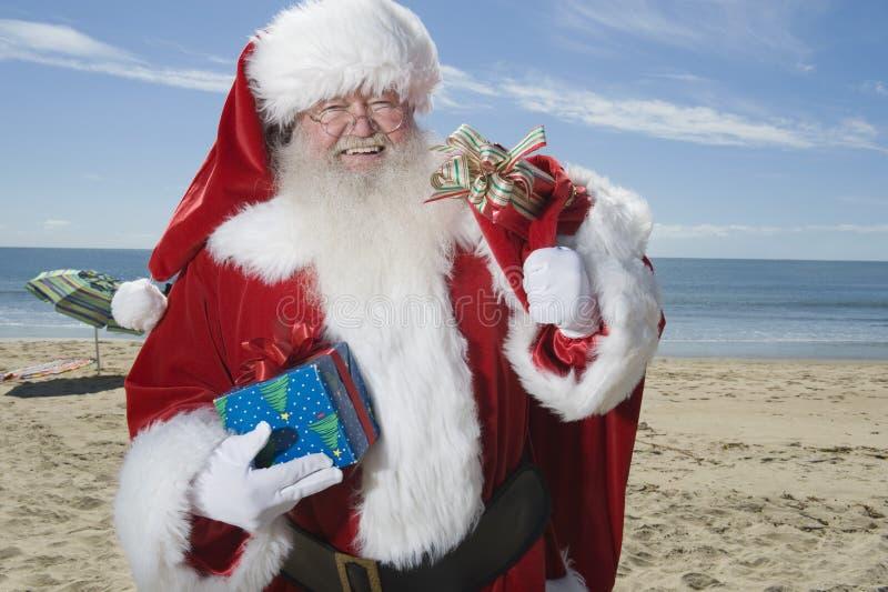 父亲圣诞节站立与他的在海滩的大袋 免版税库存图片