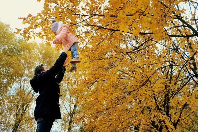 父亲在公园在秋天投掷孩子 免版税图库摄影