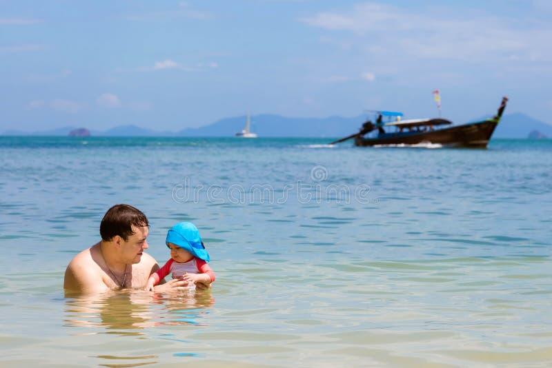 父亲在水中使用与他的女儿海上 速度longtail在背景的小船航行 库存照片