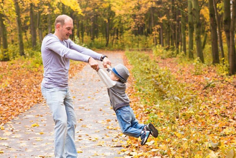 父亲在秋天公园投掷他愉快的笑的儿子 免版税图库摄影