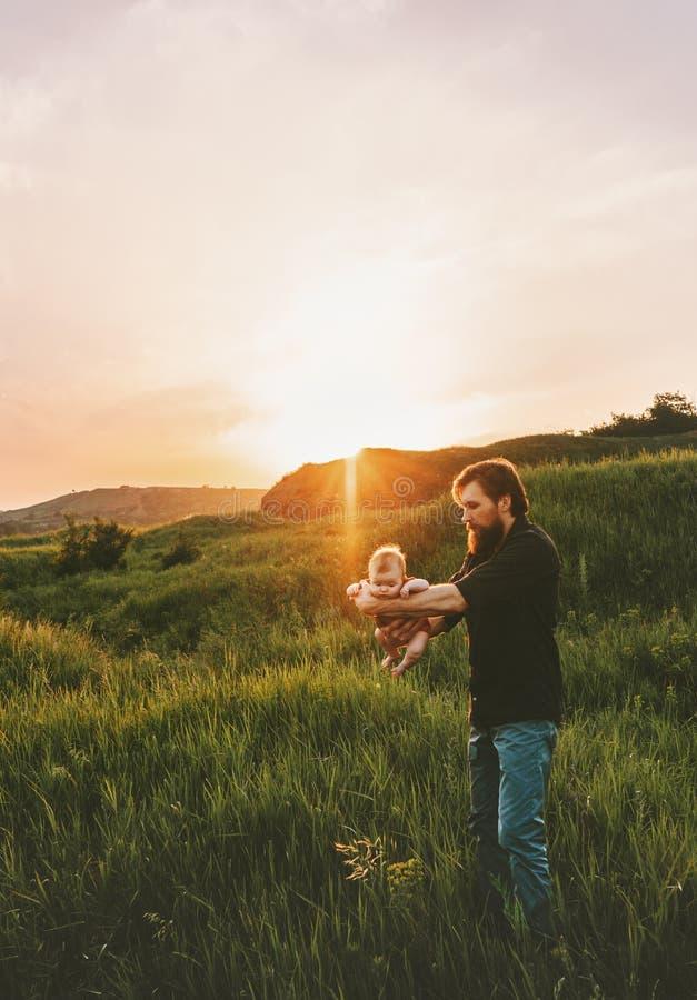 父亲在走在山的草上的藏品婴孩 免版税库存照片
