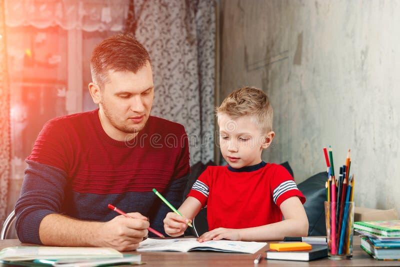 父亲帮助他的儿子做学校的家庭作业 库存图片