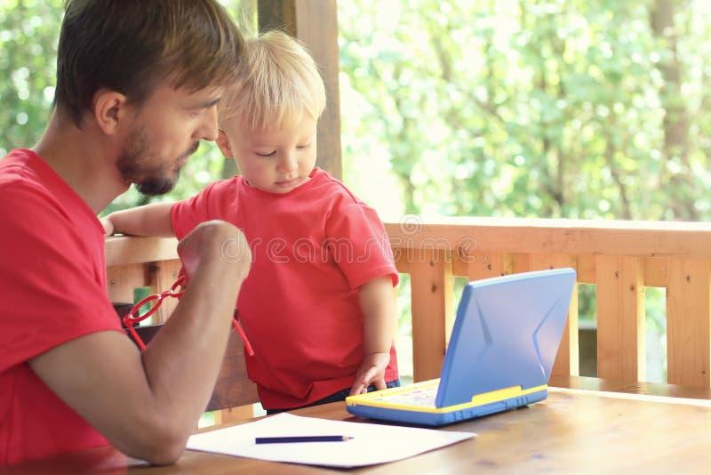 父亲帮助他的小孩儿子学会研究玩具膝上型计算机 学龄前教育或家教概念 复制空间 库存照片
