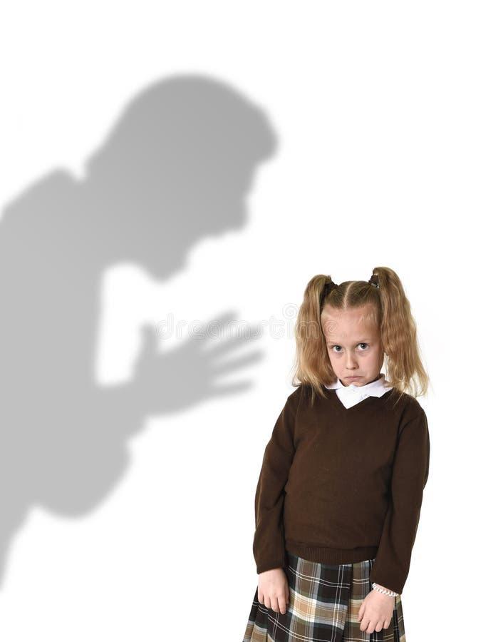 父亲或老师阴影叫喊的恼怒的责备的年轻甜矮小的女小学生或女儿 图库摄影