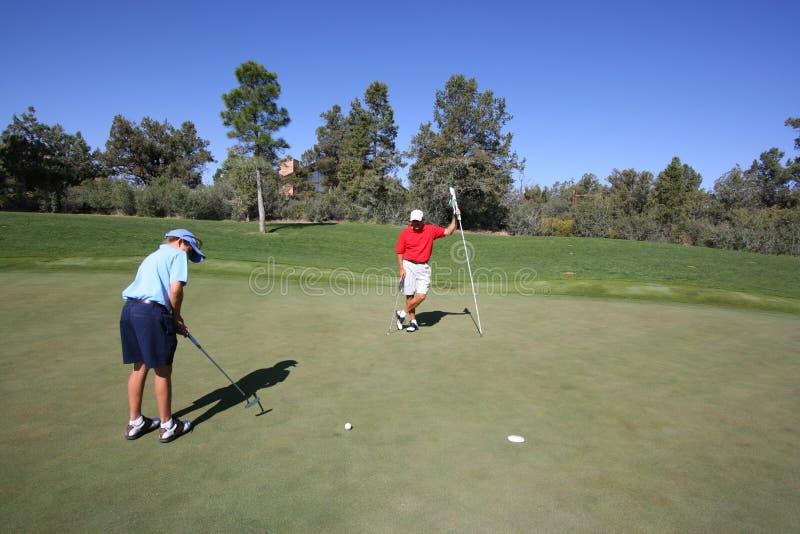父亲打高尔夫球的儿子 免版税库存照片