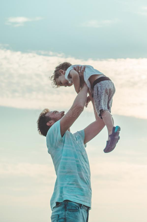 父亲投掷他新鲜空气的逗人喜爱和小儿子 生` s天、的父亲和拥抱他的儿子的男婴使用和户外 库存图片