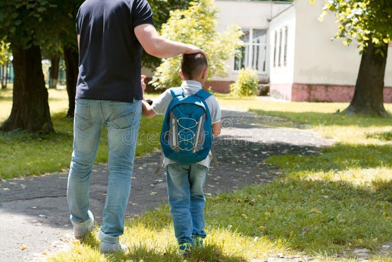 父亲护航儿子到学校 库存照片