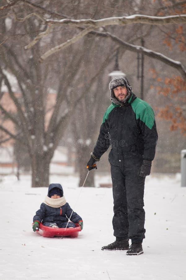父亲拉扯雪撬的一个孩子 父亲和儿子sledding在冬时 库存照片