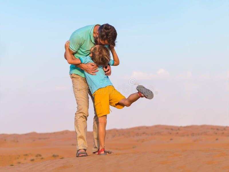 父亲拥抱一次旅行的小儿子在无边的沙漠 橙色沙子, 免版税图库摄影