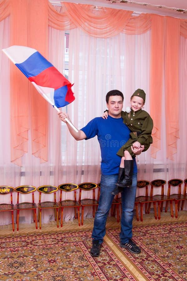 父亲拿着他的胳膊和挥动的旗子的女儿 免版税库存图片