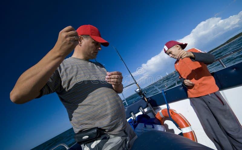 父亲捕鱼海运儿子 免版税库存照片