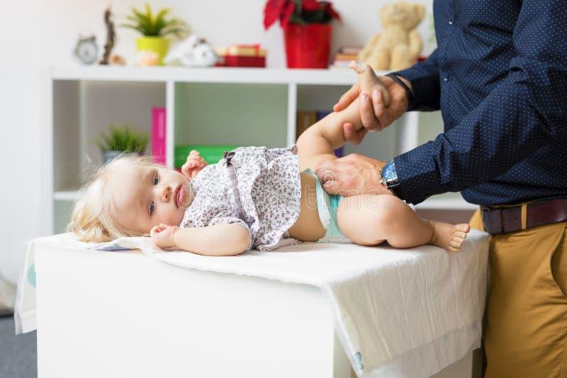 父亲改变的尿布女婴 库存图片