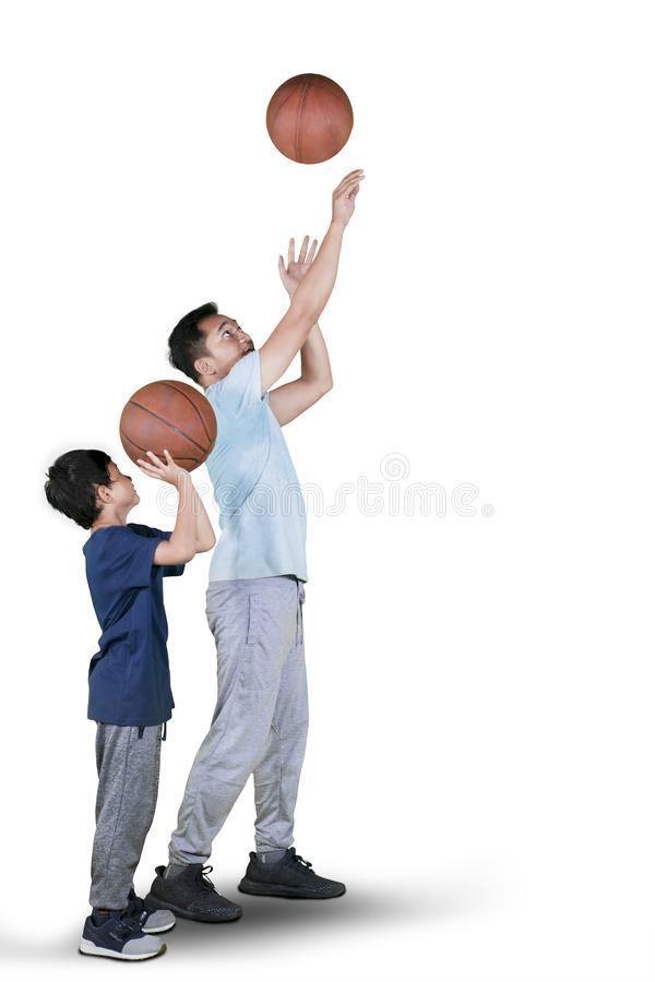 父亲教他的儿子对射击篮球 免版税图库摄影
