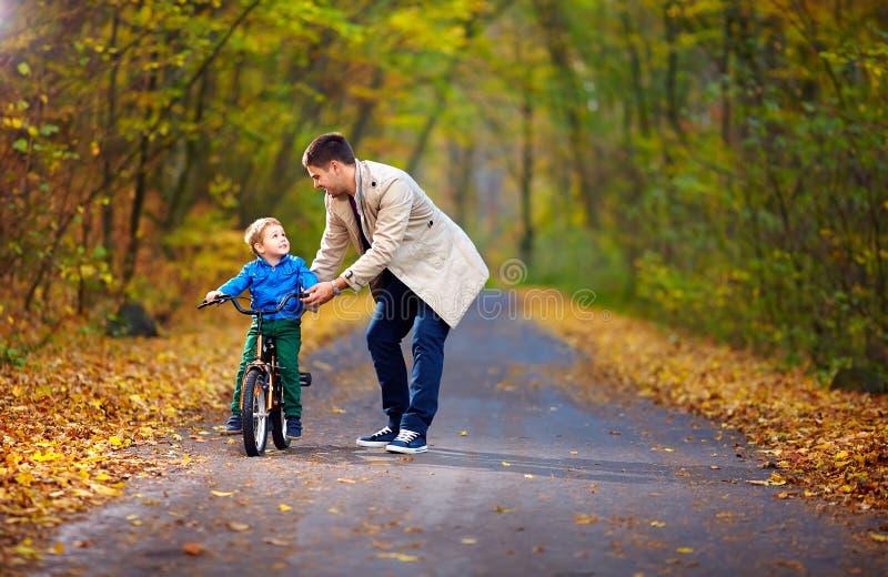 父亲教儿子骑自行车 免版税图库摄影