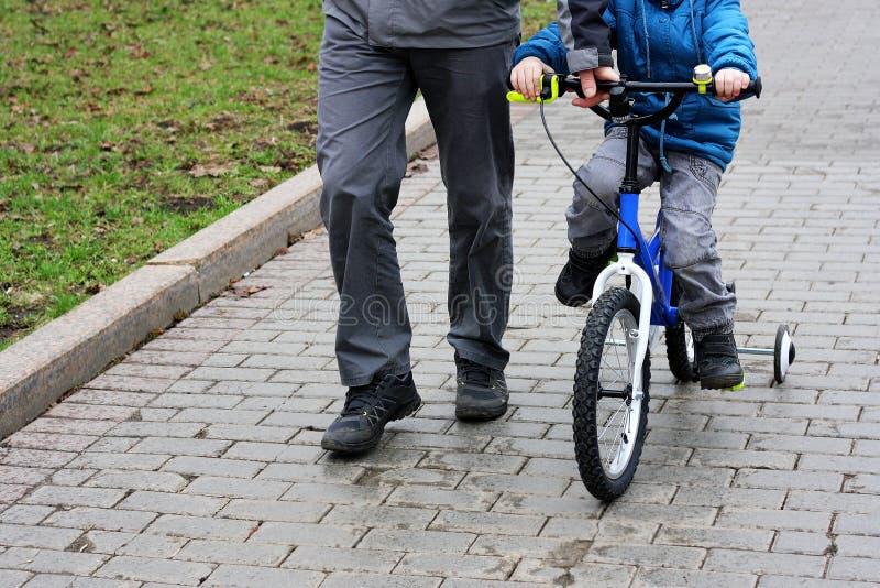 父亲教儿子骑自行车 免版税库存照片