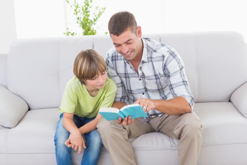 父亲男孩的读书故事沙发的 库存照片
