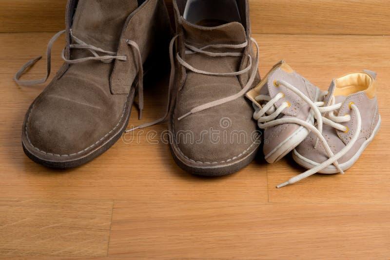父亲的鞋子特写镜头接近儿童的鞋子的 库存照片