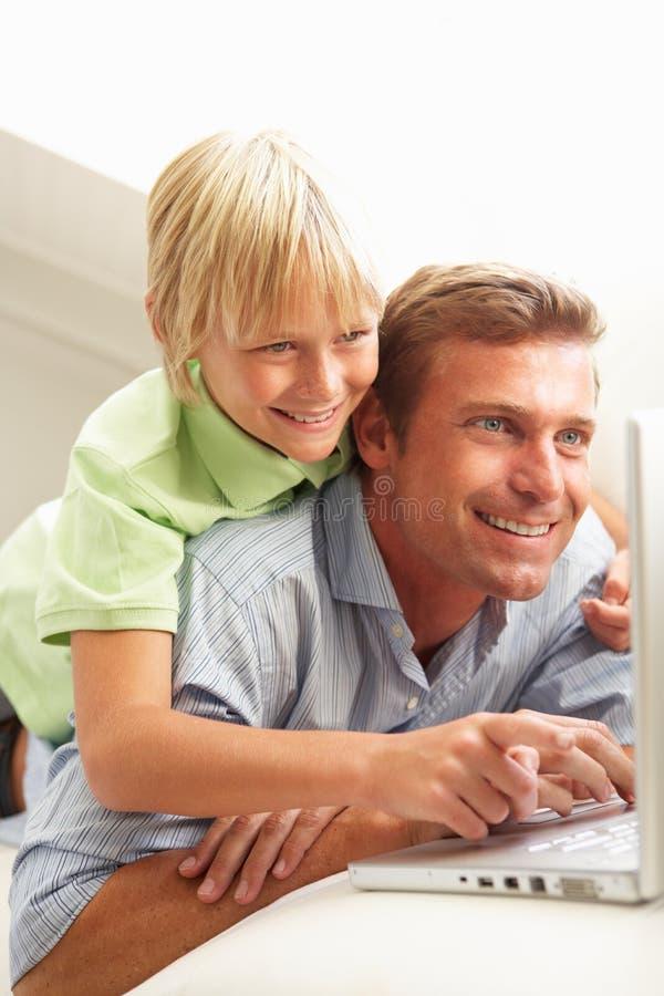 父亲膝上型计算机坐的沙发儿子使用 免版税库存照片