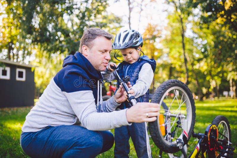 父亲节白种人爸爸和五岁的儿子在房子附近的后院在修理自行车的草坪的绿草的, 图库摄影
