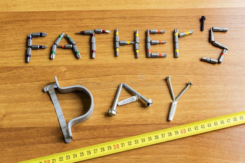 父亲节被计划一套螺丝刀和螺丝在一张木桌上 平的被放置的看法特写镜头 免版税库存图片