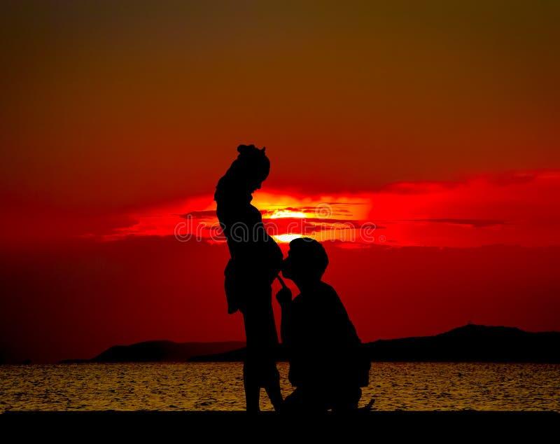 父亲节:现出轮廓年轻父亲谈话对儿子或daugh 图库摄影